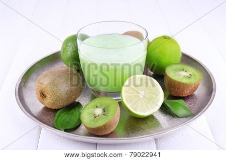 Glass of fresh lime juice with pieces of lime and kiwi on metal tray, on wooden surface background