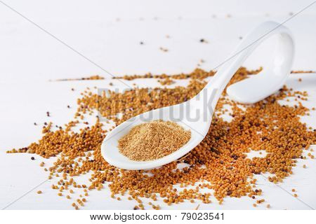 Mustard powder in spoon on mustard seeds, on  wooden background