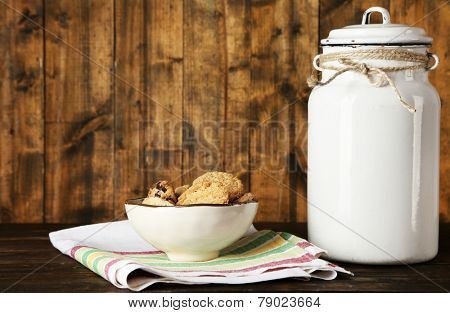Milk can with bowl of cookies on dishcloth on rustic wooden background