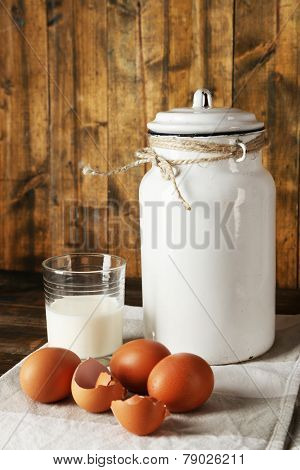 Milk can with eggs, eggshell and glass on rustic wooden background