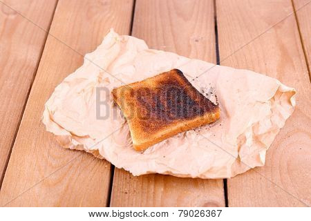 Burnt toasted bread on piece of paper and wooden table background