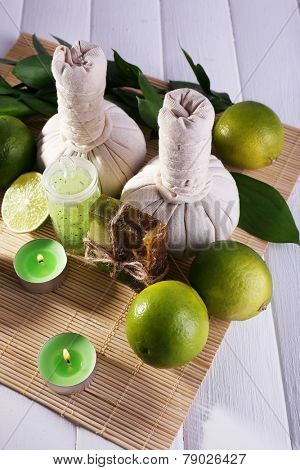 Spa composition with lime and compress balls on bamboo mat and color wooden background