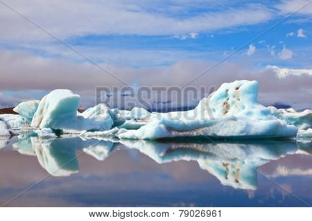 Ocean ice lagoon Yokulsarlon. Icebergs and ice floes are reflected in smooth water. Iceland in July