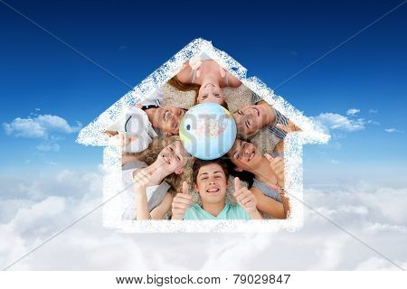 Teenagers on the floor with a terrestrial globe in the center and with thumbs up against bright blue sky over clouds