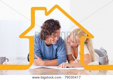 Smiling couple moving in a new house against house outline