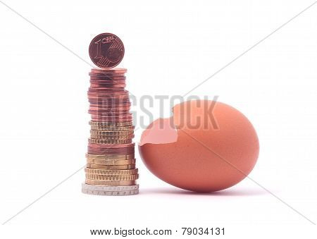 1 cent coin standing on top of stack of euro coins near cracked egg shell