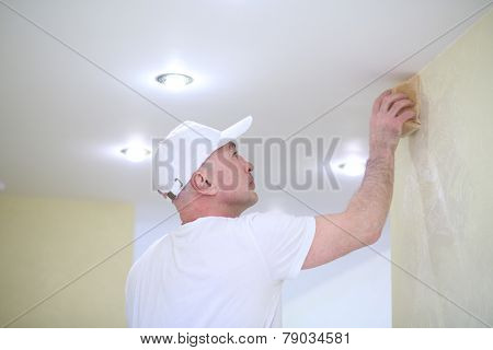 Finisher polishing the wall near the ceiling using a sanding sponge