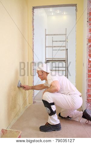 Builder sitting on the floor inflicts the plaster on the wall using a pallet