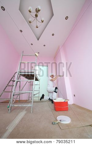 Builder with a brush in hand painted walls in pink room