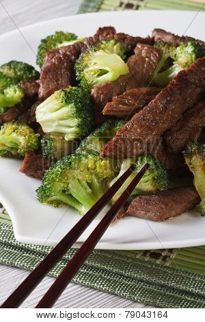 Pieces Of Beef With Broccoli Close-up And Chopsticks. Vertical