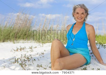 Attractive Elegant Senior Woman Sitting In Swimming Costume At Beach