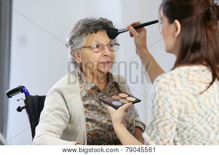 Home carer helping elderly woman to put makeup on