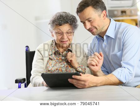 Man with elderly woman using digital tablet