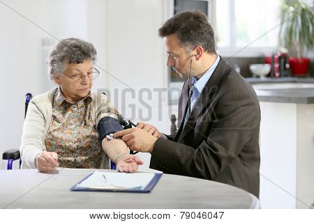 Doctor visiting elderly woman at home