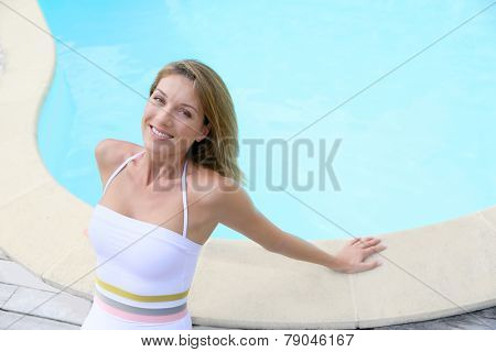 Attractive blond woman in swimsuit relaxing by pool
