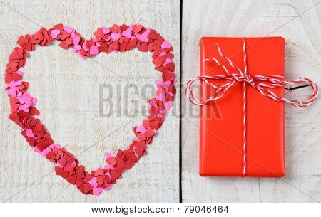 Mini paper hearts in the shape of a larger heart and a wrapped present on a rustic wooden table. Perfect for Love and Valentines Day concepts. Horizontal format.