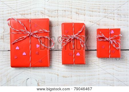 Overhead shot of three of Valentines Day presents wrapped in red paper tied with string and mini red paper hearts on a rustic wood table. Horizontal format.