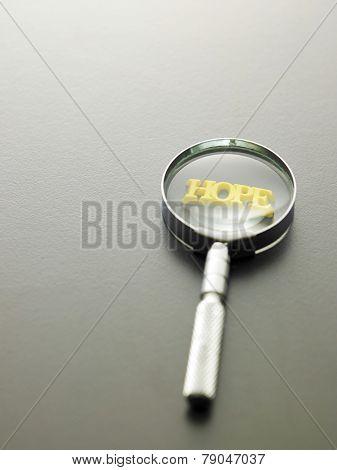 magnifying glass focus on alphabet hope