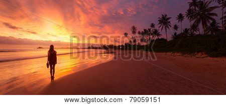 Lady walking on the wet sandy beach during sunset