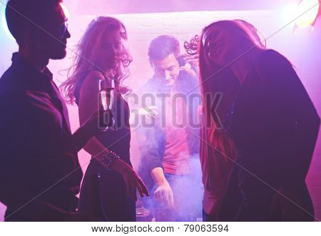 Deejay working and cool girls dancing in nightclub