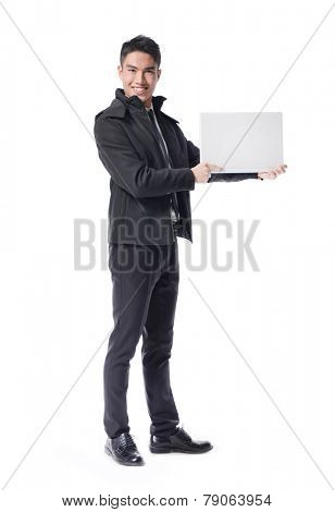 Full body young businessman using laptop against white background. Horizontal shot