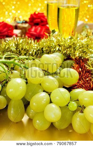 closeup of a bunch of grapes and glasses with champagne and some gifts in the background for the traditional celebration of the New Year in Spain