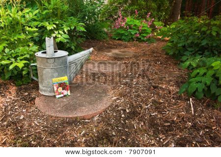 A Worn Watering Can Sits With A Hollyhock Seed Packet On A Garden Path