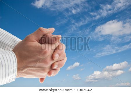 Praying Hand In Front Of A Blue Sky