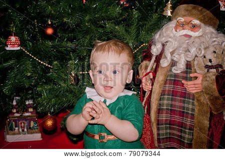 Little Baby Biy Sits Under Decorated Christmas Tree With Santa