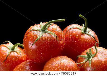 Selection of fresh, ripe red tomatoes framed against a black background for placement of copy.
