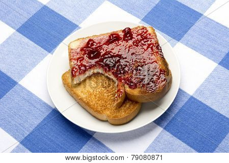 Fresh, hot toast spread with grape jelly sits with a bite taken out of it during mealtime.