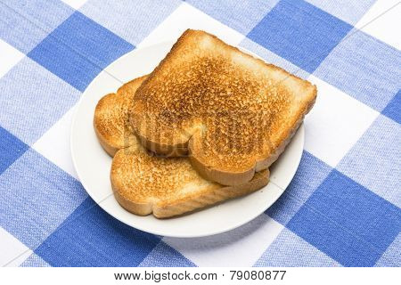 Two slices of fresh, white toast on a plate and checkered blue and white tablecloth