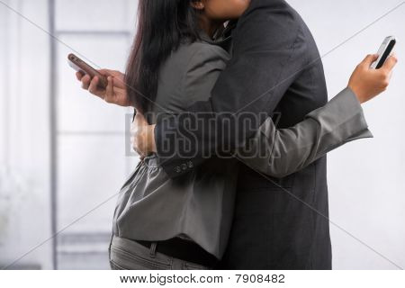 Business Couple Hug Yet Still Using Cell Phone