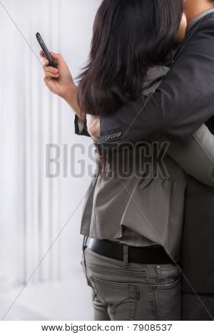 Business Couple Hug Yet The Man Still Using Cell Phone