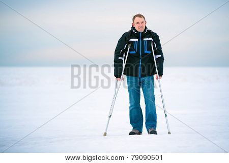 Man with crutches walking outdoors