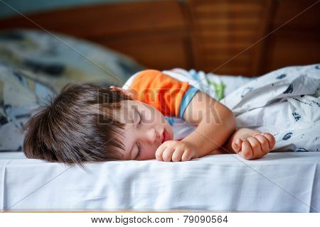 Cute little boy sleeping in a bed