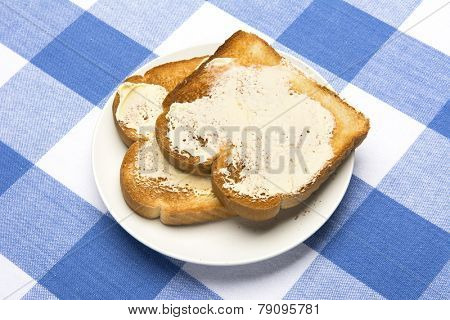 Fresh, hot toast spread with butter sits during mealtime to be consumed.