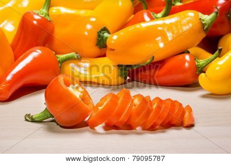 Fresh, colorful mini bell peppers on a chopping board being chopped for use as a cooking ingredient