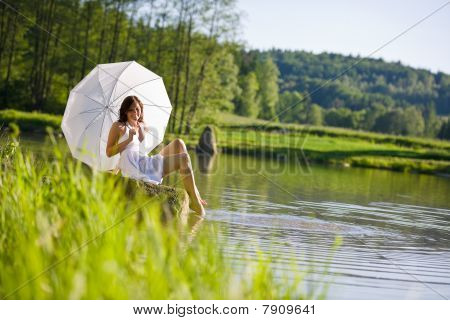 Happy Romantic Woman Sitting By Lake With Parasol