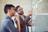 image of reminder  - Asian manager pointing at reminder while talking to colleague in office - JPG