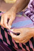picture of stitches  - Woman hand stitching cloth to make ancient Thai pattern fabric - JPG