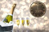 stock photo of count down  - Clock counting down to midnight against champagne cooling in ice bucket - JPG