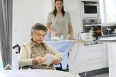 picture of laundry  - Elderly woman reading book while home helper irons laundry - JPG
