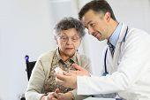 stock photo of prescription  - Doctor with elderly woman showing medical prescription - JPG