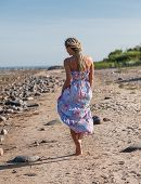 stock photo of minx  - Happy young woman with dreadlocks walking along the seashore - JPG
