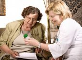stock photo of nurse practitioner  - Senior woman is visited by her doctor or caregiver at home - JPG