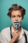 pic of razor  - Cute brunette woman in hair curlers playing fool with foam on face shaving with razor on her tongue - JPG
