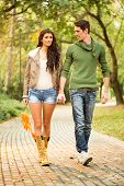 picture of short legs  - Young pretty girl with long legs in shorts and boots holding hands with her handsome boyfriend walking trails in the park - JPG