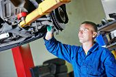 foto of suspension  - car mechanic worker repairing suspension of lifted automobile at auto repair garage shop station - JPG