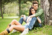 foto of leggy  - Young handsome guy and attractive leggy girl sitting on the grass in the park - JPG